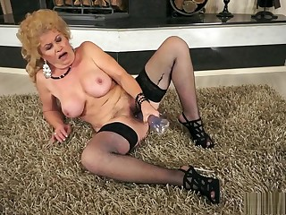 Lustful granny in black stockings uses a glass dildo to find pleasure